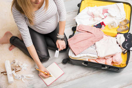 Pregnant woman packing for hospital and taking notes