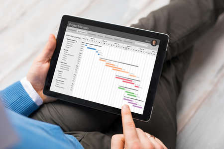 Man using project management app on tablet computer Foto de archivo