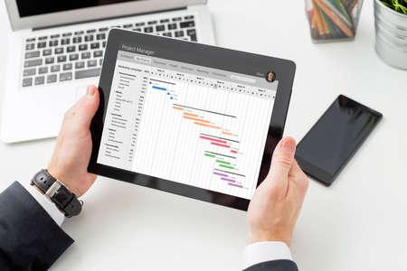 사업가 태블릿 컴퓨터에서 Gantt 차트를보고