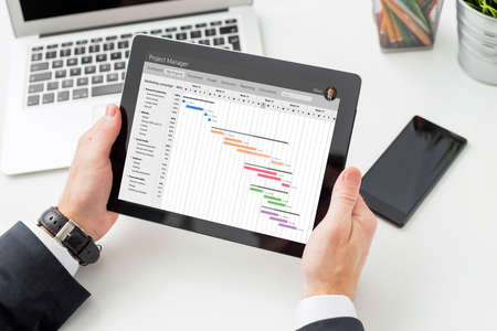 Businessman looking at Gantt chart on tablet computer Stock Photo