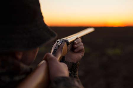 Hunter aiming shotgun in dusk