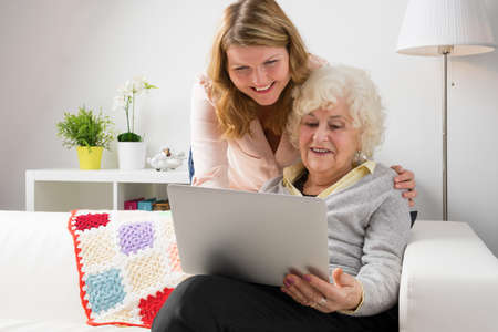 Grandaughter teaching grandma how to use modern computer