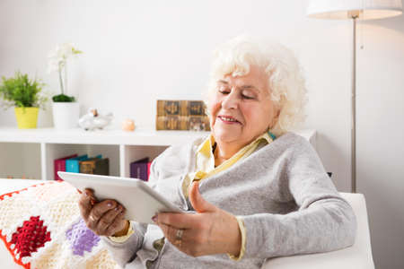 new age: Grandmother using tablet computer in her living room