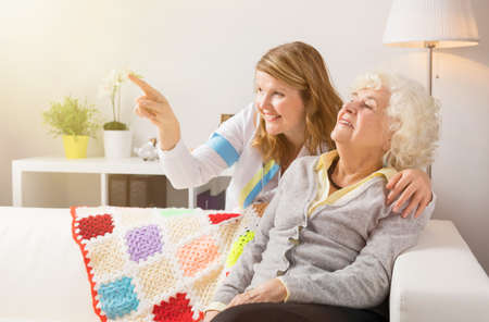 proffessional: Grandma and health proffessional looking at something Stock Photo