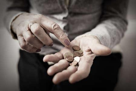Oudere persoon telt geld in haar palm Stockfoto