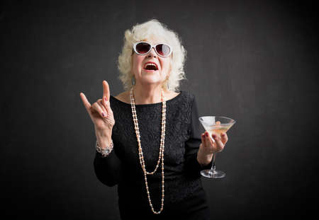 Cool grandmother with sunglasses and drink in hand Standard-Bild