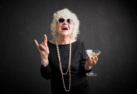 Koel oma met zonnebril en drink in de hand Stockfoto