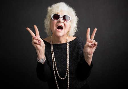 Koele grootmoeder die vredesteken toont