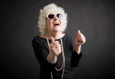 Koele oma met haar duimen omhoog