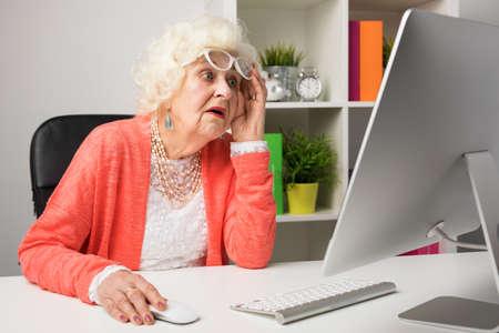 Oma werkt op kantoor en kijkt ongelovig naar de computer