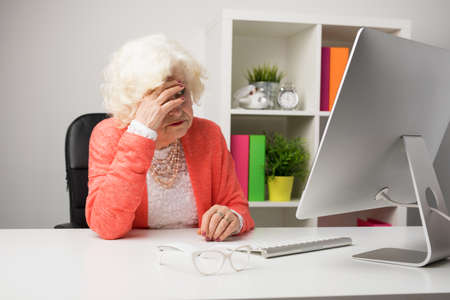 Older woman at the office having headache Stock Photo
