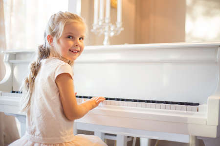 Little girl playing piano Reklamní fotografie - 72775594