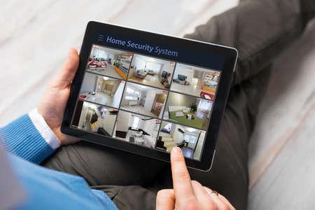 タブレット コンピューターの家庭で防犯カメラを見ている男