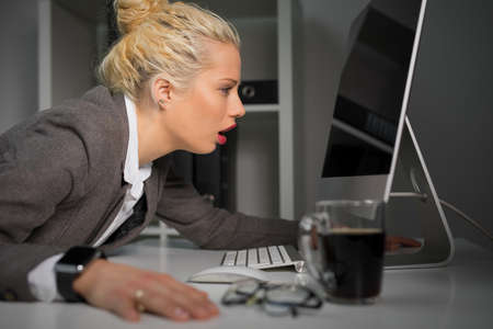 overwrought: Exhausted and tired woman looking at computer screen very close Stock Photo