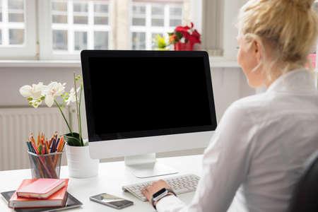 Vrouw in kantoor werken op stationaire computer Stockfoto