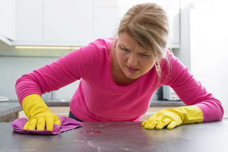 ocd: Woman clening a stain on kitchen counter