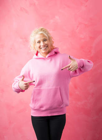 Woman in pink sweater pointing at it with both hands