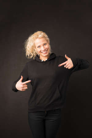 Woman in black hoodie pointing with both hands at it