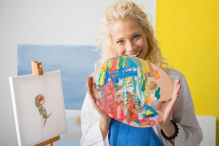 Woman artist holding color palette in her studio