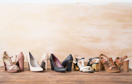 Different womans shoes on wooden floor