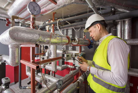 Man in helmet writing down measurements in heat and airconditioning system panel