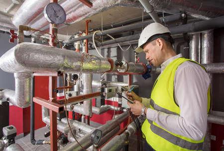 Man in helm met afmetingen in warmte en airconditioning systeempaneel Stockfoto