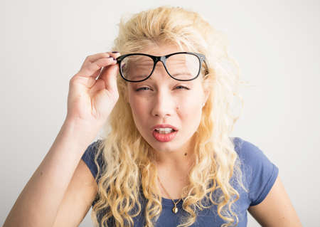 Woman with her glasses lifted up can't see Stockfoto
