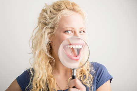 Woman showing her smile through magnifying glass