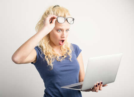 Woman in shock looking at laptop