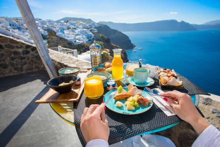 sea view: Woman having breakfast in Santorini, Greece