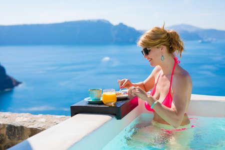 woman bath: Woman having breakfast while relaxing in outdoor bathtub