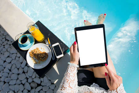 Woman using digital tablet while sitting in swimming pool Reklamní fotografie - 78962865