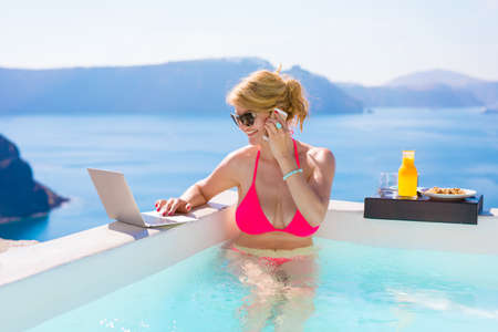 Busy business woman working while on vacation in pool Stock Photo