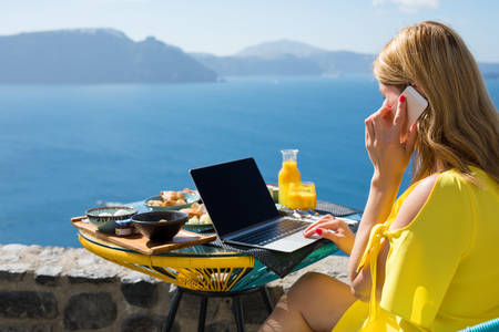 Woman working while on vacation in Mediterranean Imagens