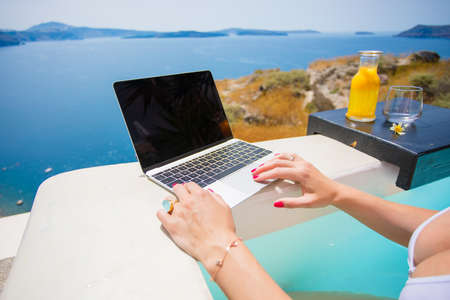 Woman using laptop while resting in pool Stock Photo