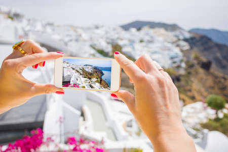 Tourist taking picture of Santorini with mobile phone 免版税图像