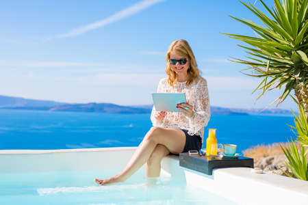 Woman using tablet while sitting by the pool Stock Photo