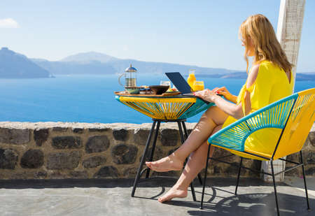 Woman working on computer while on vacation in Mediterranean Standard-Bild