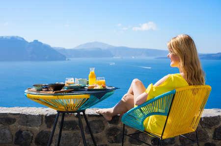 테라스에서 아름 다운 경치와 함께 고급스러운 아침 식사를 즐기는 여자 스톡 콘텐츠