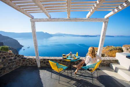サントリーニ島の美しい景色と朝食を楽しむ女性