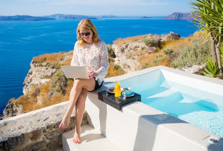 Woman using laptop while sitting by the pool