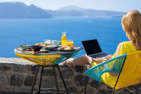 아침 식사를하는 동안 랩톱 컴퓨터를 사용하는 여성