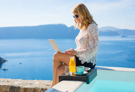 Woman working on computer while sitting by the pool Stock Photo