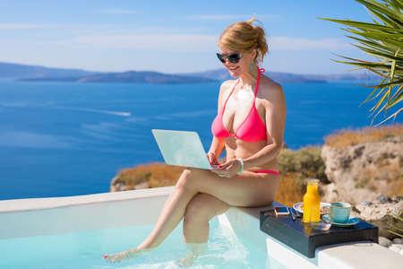 Woman in pink bikini using laptop