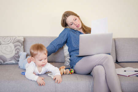 Working mom with baby on the couch, working on laptop and talking on the phone