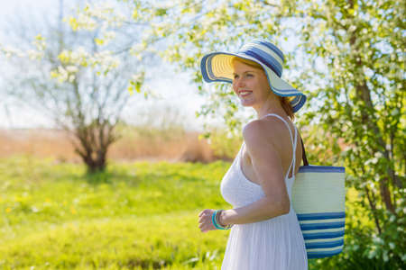 bright woman standing outdoors and enyoing weather