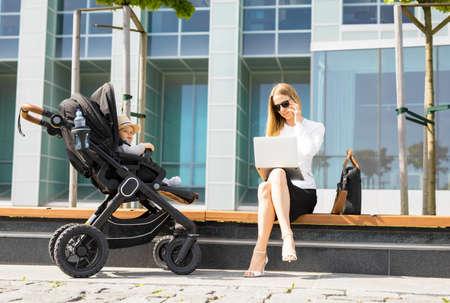 Bedrijfs vrouw die op de telefoon spreekt en aan laptop outdors werkt terwijl het hebben van een baby in wandelwagen