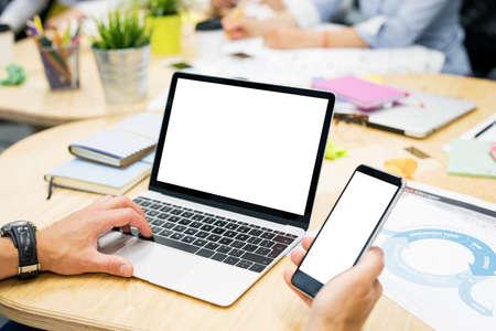 Man aan het werk op laptop en mobiele telefoon Stockfoto