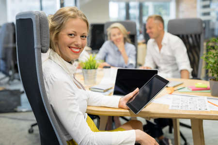 Woman in office holding tablet with co-workers in background