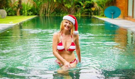 Happy woman enjoying Christmas holidays in tropical pool
